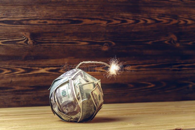 Βόμβα των χρημάτων όπως το δυναμίτη, λογαριασμοί εκατό-δολαρίων με μια καίγοντας θρυαλλίδα Έννοια της οικονομικής κρίσης στοκ φωτογραφία