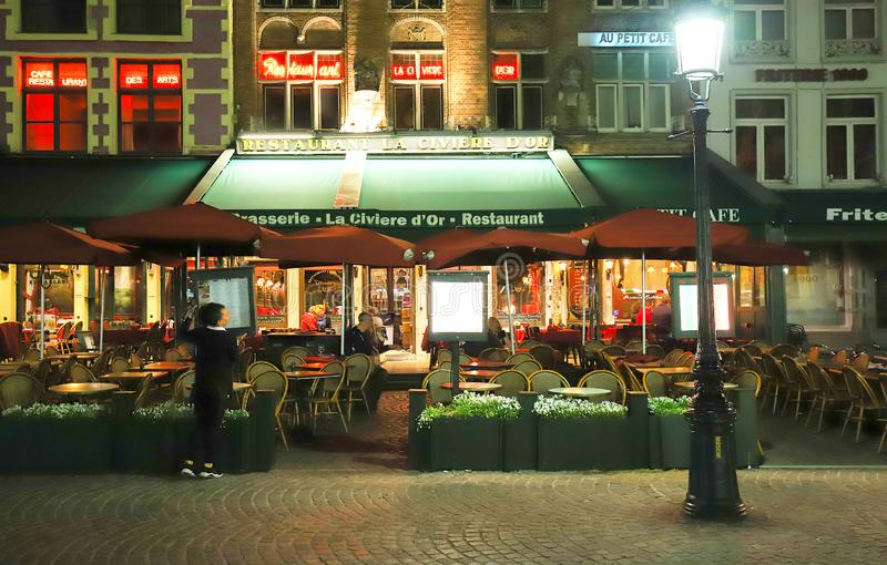 Βόρεια πλευρά εικόνας νύχτας της πλατείας Grote Markt με τους γοητευτικούς καφέδες οδών, χώρος συνάντησης του Brugelings και τουρ στοκ εικόνα