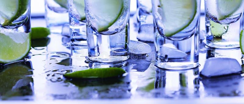 Βότκα κινηματογραφήσεων σε πρώτο πλάνο σε ένα γυαλί με τον πάγο, βότκα ασβέστη, τζιν, τονωτικό, tequila στοκ εικόνες