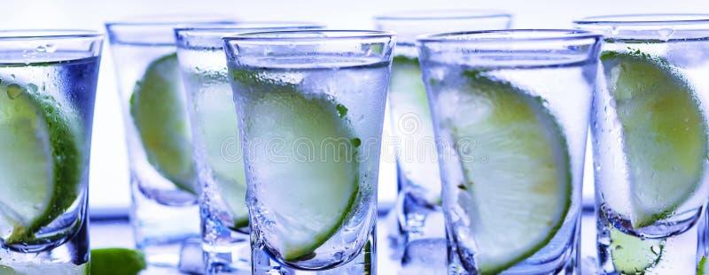 Βότκα κινηματογραφήσεων σε πρώτο πλάνο σε ένα γυαλί με τον πάγο, βότκα ασβέστη, τζιν, τονωτικό, tequila στοκ εικόνα με δικαίωμα ελεύθερης χρήσης