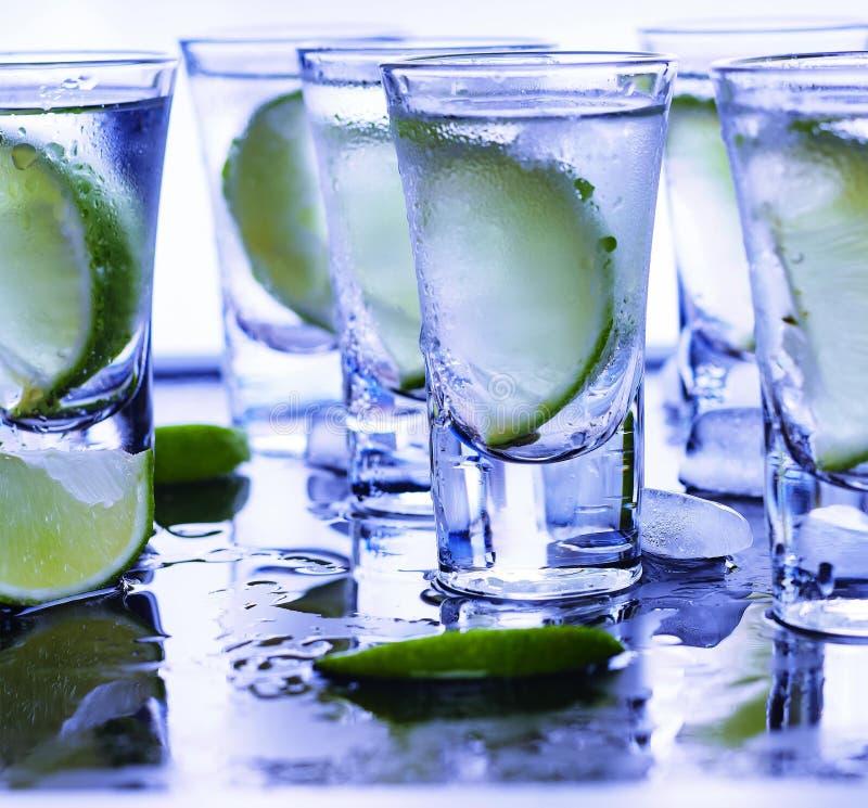Βότκα κινηματογραφήσεων σε πρώτο πλάνο σε ένα γυαλί με τον πάγο, βότκα ασβέστη, τζιν, τονωτικό, tequila στοκ φωτογραφία