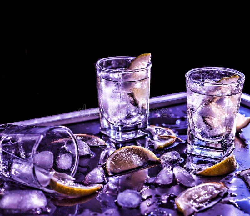 Βότκα κινηματογραφήσεων σε πρώτο πλάνο σε ένα γυαλί με τον πάγο, βότκα ασβέστη, τζιν, τονωτικό, tequila στοκ εικόνα