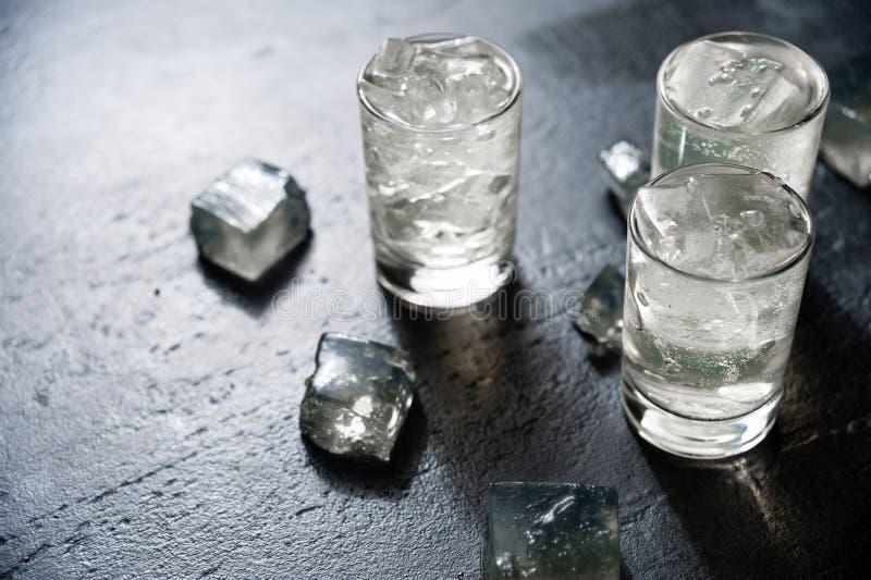 Βότκα κινηματογραφήσεων σε πρώτο πλάνο σε ένα γυαλί με τον πάγο, τζιν, τονωτικό, tequila στοκ εικόνα