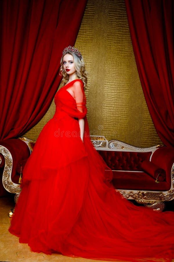 Βλαστός μόδας της όμορφης ξανθής γυναίκας σε ένα μακρύ κόκκινο φόρεμα στο εκλεκτής ποιότητας κόκκινο υπόβαθρο καναπέδων στοκ εικόνα