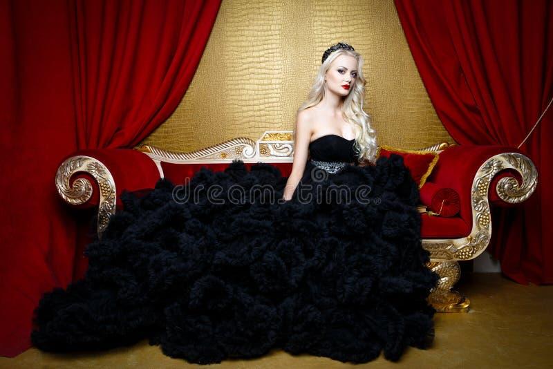 Βλαστός μόδας της όμορφης ξανθής γυναίκας σε μια μακροχρόνια μαύρη συνεδρίαση φορεμάτων στον καναπέ στοκ φωτογραφία
