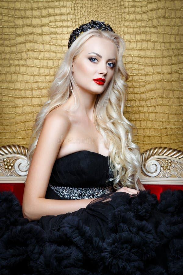 Βλαστός μόδας της όμορφης ξανθής γυναίκας σε μια μακροχρόνια μαύρη συνεδρίαση φορεμάτων στον καναπέ στοκ εικόνες