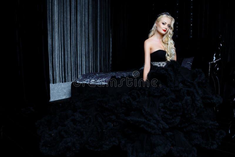 Βλαστός μόδας της όμορφης ξανθής γυναίκας σε μια μακροχρόνια μαύρη συνεδρίαση φορεμάτων στον καναπέ στοκ φωτογραφία με δικαίωμα ελεύθερης χρήσης