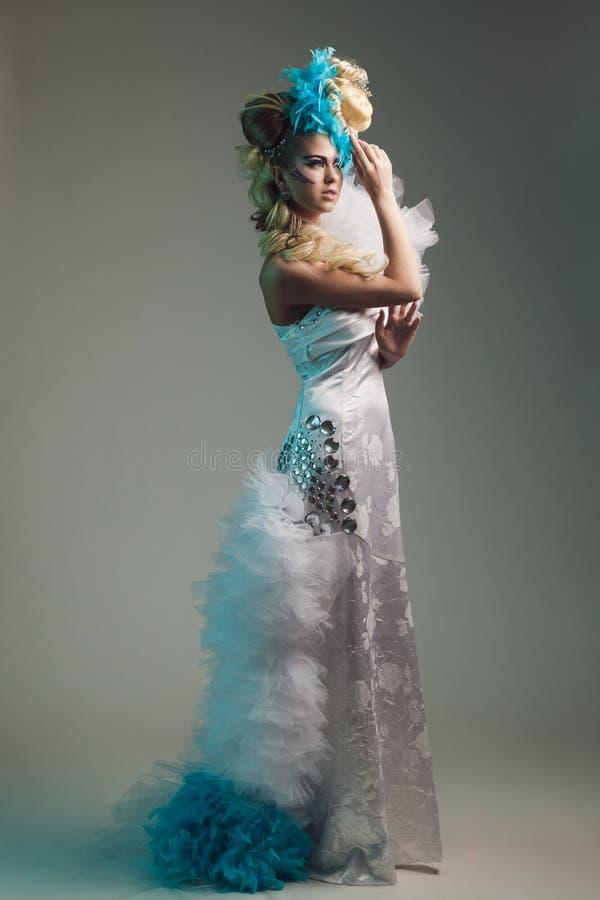 Βλαστός στούντιο της γυναίκας με το δημιουργικά hairstyle, makeup και το φόρεμα στοκ φωτογραφία