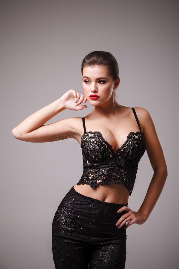 Βλαστός στούντιο της ελκυστικής γυναίκας στην προκλητικά μαύρα κορυφή και το παντελόνι στοκ φωτογραφίες