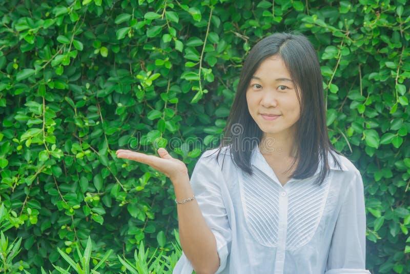 Βλαστών άσπρο πουκάμισο ένδυσης πορτρέτου γυναικών φωτογραφιών ασιατικό, που κρατά το ανοικτό χέρι και που χαμογελά με το πράσινο στοκ φωτογραφία με δικαίωμα ελεύθερης χρήσης