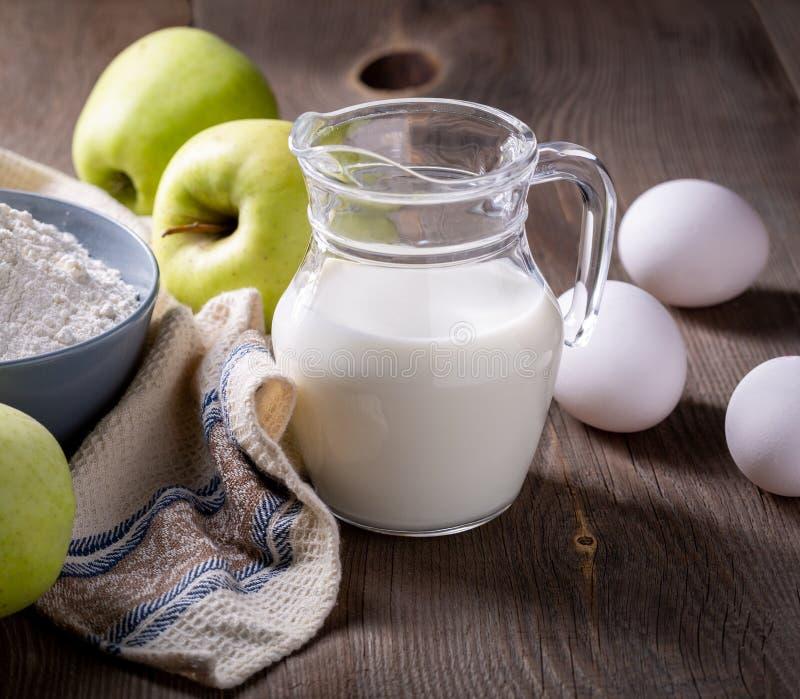 Γάλα, αλεύρι, αυγά και πράσινα μήλα σε ξύλινο τραπέζι Συστατικά για τη σαρλότα μήλων στοκ φωτογραφία με δικαίωμα ελεύθερης χρήσης