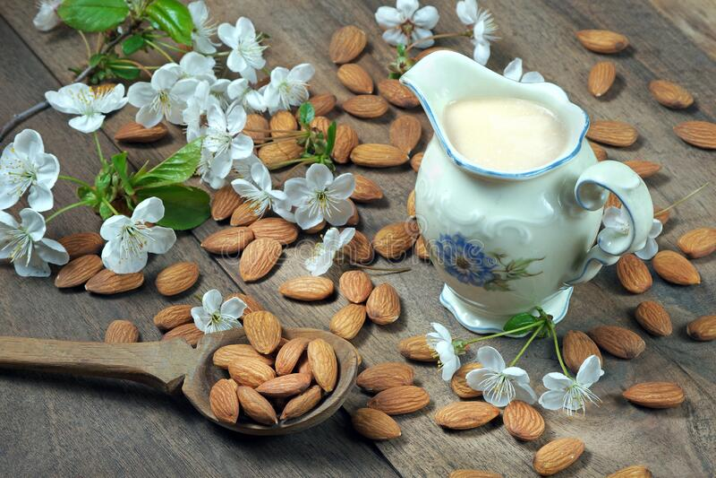 Γάλα αμυγδάλου σε βάζο, αμύγδαλα στο τραπέζι και λευκά άνθη ανοιξιάτικης πηγής στοκ εικόνα με δικαίωμα ελεύθερης χρήσης