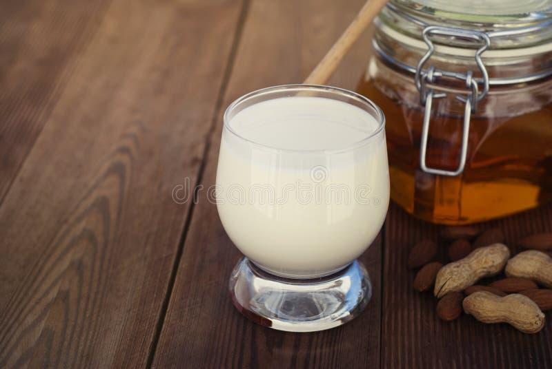 Γάλα αμυγδάλων στο γυαλί με τα αμύγδαλα στον ξύλινο πίνακα, αγροτικό ύφος στοκ φωτογραφία με δικαίωμα ελεύθερης χρήσης