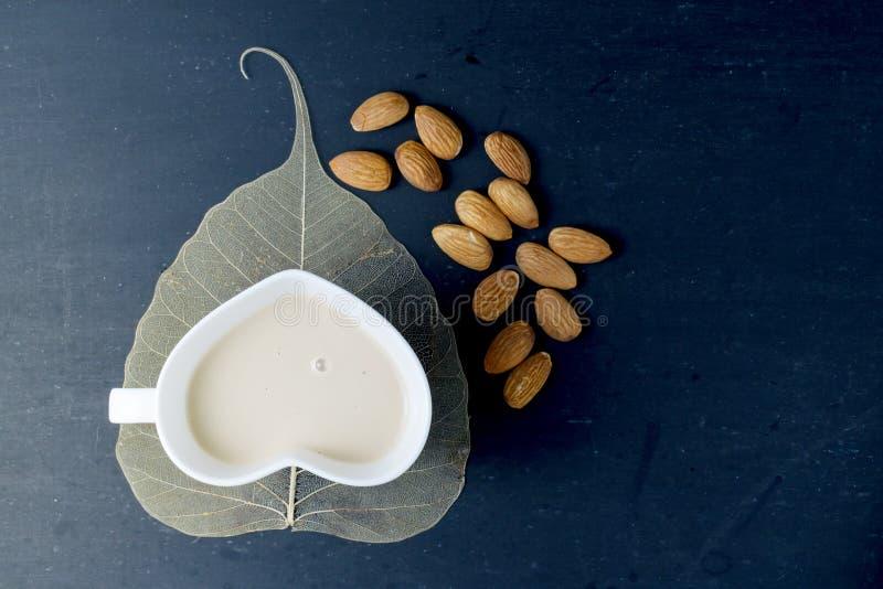 Γάλα αμυγδάλων στο γυαλί μορφής καρδιών στοκ φωτογραφία