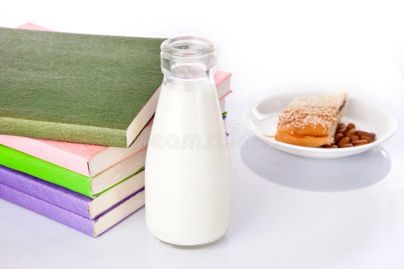 Γάλα, βιβλία και πρόχειρα φαγητά στοκ φωτογραφίες