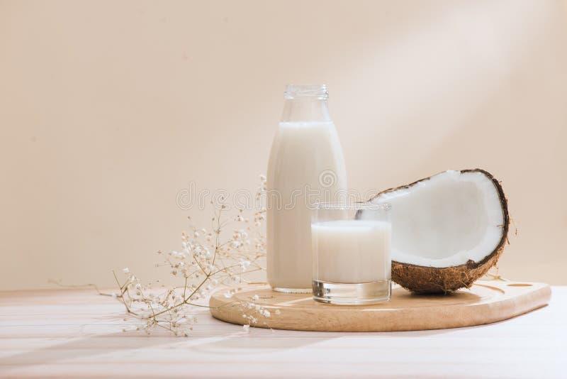 Γάλα καρύδων στο μπουκάλι και γυαλί στον πίνακα με το διάστημα αντιγράφων στοκ εικόνες με δικαίωμα ελεύθερης χρήσης