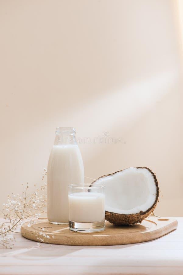 Γάλα καρύδων στο μπουκάλι και γυαλί στον πίνακα με το διάστημα αντιγράφων στοκ φωτογραφία