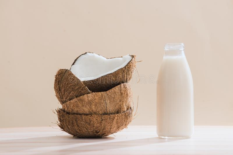 Γάλα καρύδων στο μπουκάλι και γυαλί στον πίνακα με το διάστημα αντιγράφων στοκ εικόνα