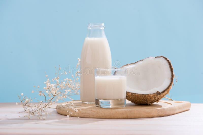 Γάλα καρύδων στο μπουκάλι και γυαλί στον πίνακα με το διάστημα αντιγράφων στοκ φωτογραφία με δικαίωμα ελεύθερης χρήσης