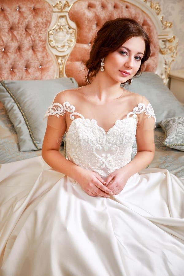 γάμος Νύφη στην όμορφη συνεδρίαση φορεμάτων στον καναπέ στο εσωτερικό στο άσπρο εσωτερικό στούντιο όπως στο σπίτι Καθιερώνον τη μ στοκ εικόνες με δικαίωμα ελεύθερης χρήσης