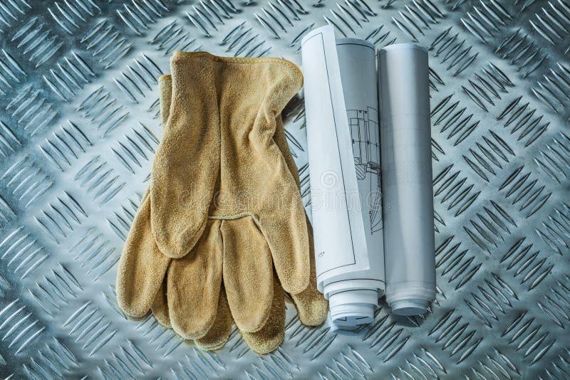 Γάντια ασφάλειας κατασκευαστικών σχεδίων στο διοχετευμένο φύλλο μετάλλων στοκ εικόνες
