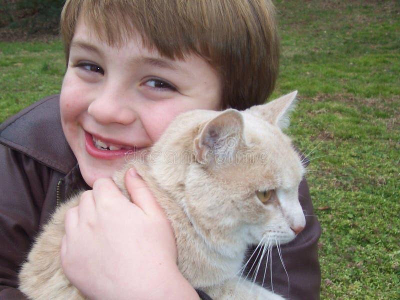 γάτα αγοριών που αγκαλιάζει το κατοικίδιο ζώο στοκ εικόνες με δικαίωμα ελεύθερης χρήσης