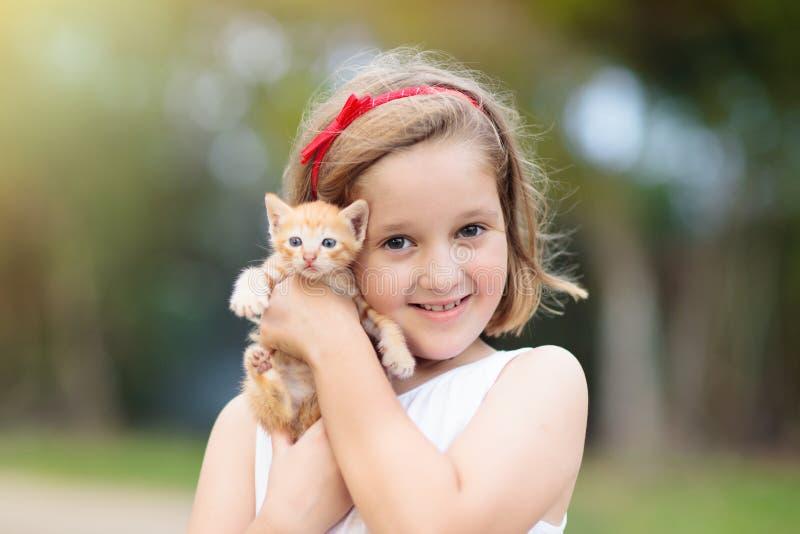 Γάτα μωρών εκμετάλλευσης μικρών κοριτσιών Παιδιά και κατοικίδια ζώα στοκ φωτογραφίες με δικαίωμα ελεύθερης χρήσης