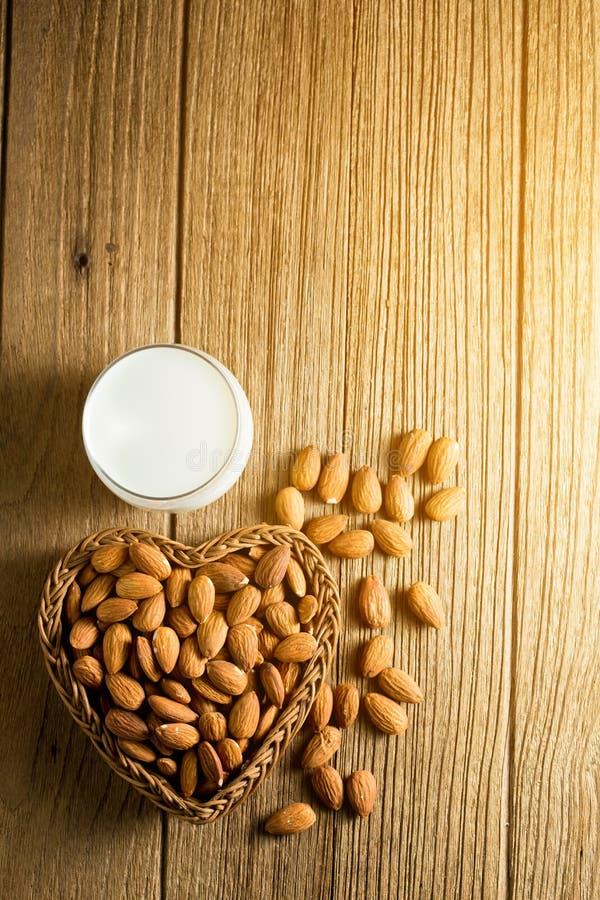 Γάλα αμυγδάλων στο γυαλί με τα αμύγδαλα στη μορφή καρδιών καλαθιών στοκ εικόνες