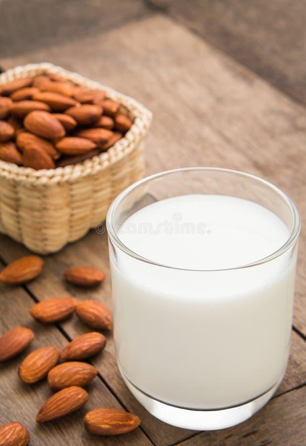 Γάλα αμυγδάλων στο γυαλί με τα αμύγδαλα στον ξύλινο πίνακα στοκ εικόνες