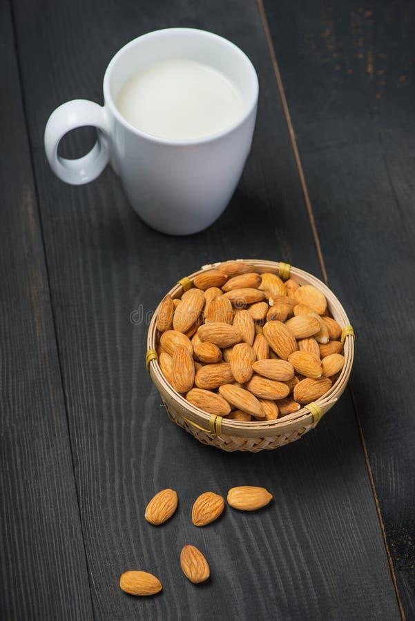 Γάλα αμυγδάλων στο γυαλί με τα αμύγδαλα στο μαύρο ξύλινο πίνακα στοκ φωτογραφία με δικαίωμα ελεύθερης χρήσης