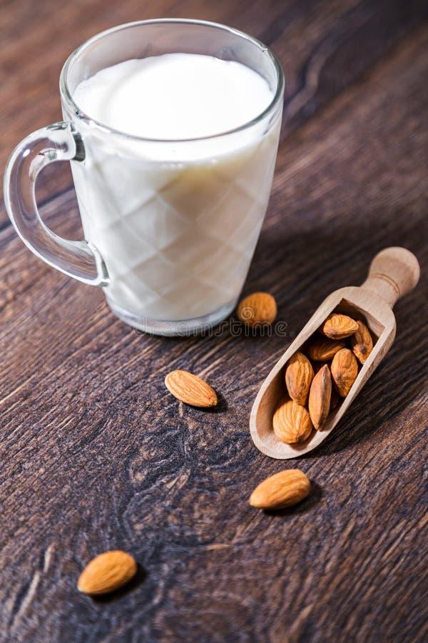 Γάλα και καρύδια αμυγδάλων πέρα από το αγροτικό ξύλινο υπόβαθρο στοκ εικόνες
