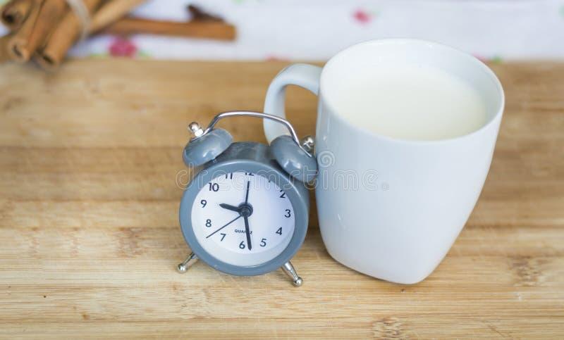 Γάλα σε ένα άσπρο φλυτζάνι με το μικρό ρολόι σε ένα ξύλινο υπόβαθρο στοκ εικόνες