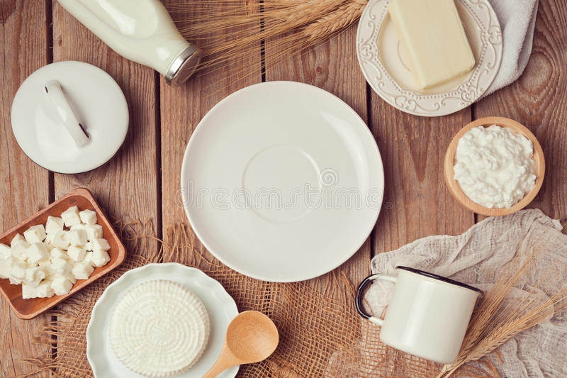 Γάλα, τυρί και βούτυρο γύρω από το κενό άσπρο πιάτο στο ξύλινο υπόβαθρο κατανάλωση έννοιας υγιής επάνω από την όψη στοκ εικόνα