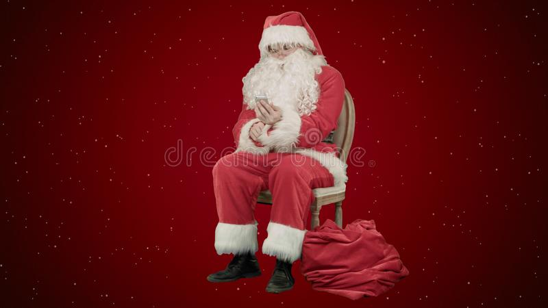 Γέλιο Santa έξω δυνατό όπως μιλά στο τηλέφωνο κυττάρων του στο κόκκινο υπόβαθρο με το χιόνι στοκ φωτογραφίες με δικαίωμα ελεύθερης χρήσης