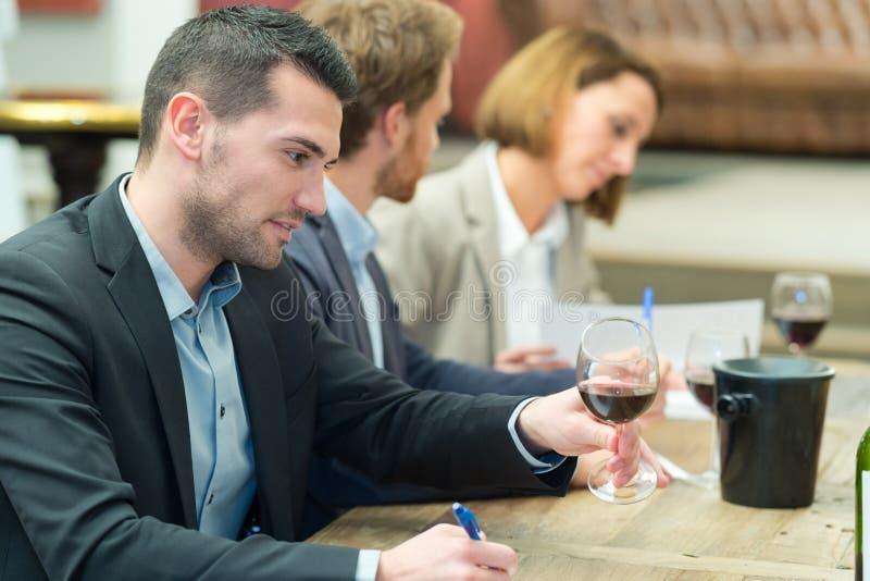 Γέρνοντας wineglass ατόμων για να εξετάσει το κρασί χρώματος στοκ εικόνα με δικαίωμα ελεύθερης χρήσης