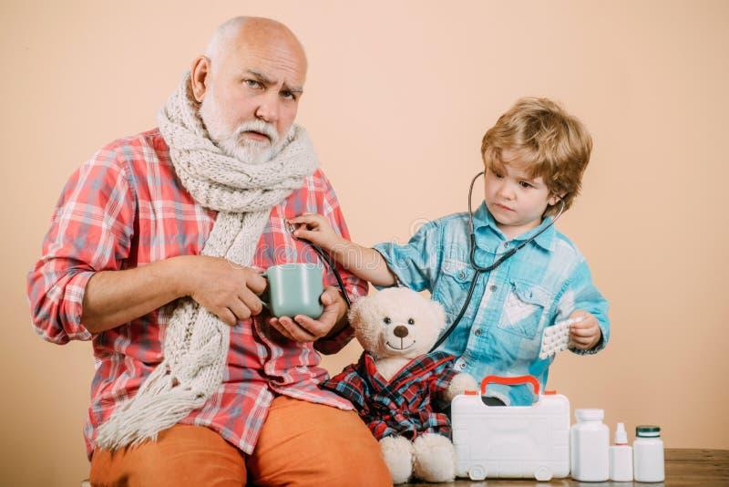 Γέρος που παίρνει ένα χάπι Άρρωστος παππούς με ένα ζεστό κασκόλ γύρω από το λαιμό του Ευτυχισμένο παιδί και παππούς με στηθοσκόπι στοκ εικόνες με δικαίωμα ελεύθερης χρήσης