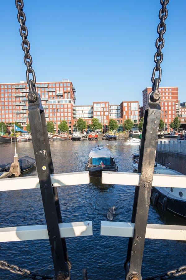 Γέφυρα αλυσίδων στο υπόβαθρο της ολλανδικής σύγχρονης πόλης του Άμστερνταμ Κάτω Χώρες Westerdok στοκ φωτογραφία