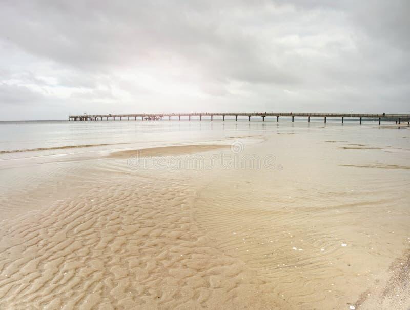 Γέφυρα θάλασσας επάνω από τη θάλασσα της Βαλτικής Ήλιος που κρύβεται στο misty ορίζοντα, στοκ εικόνες