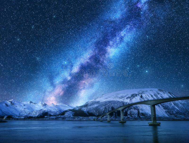 Γέφυρα και έναστρος ουρανός με το γαλακτώδη τρόπο πέρα από τα χιονισμένα βουνά στοκ φωτογραφίες