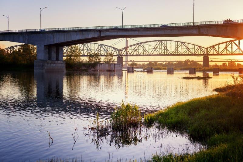 Γέφυρα και ποταμός στις ακτίνες του ήλιου ρύθμισης, όμορφη πόλη στοκ εικόνες