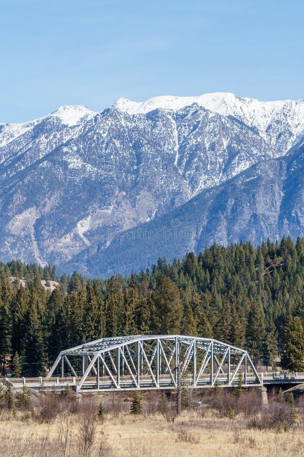 γέφυρα μετάλλων πέρα από έναν ποταμό με το βουνό στο χιόνι στην περιφερειακή περιοχή υποβάθρου της ανατολής Kootenay Καναδάς στοκ φωτογραφίες