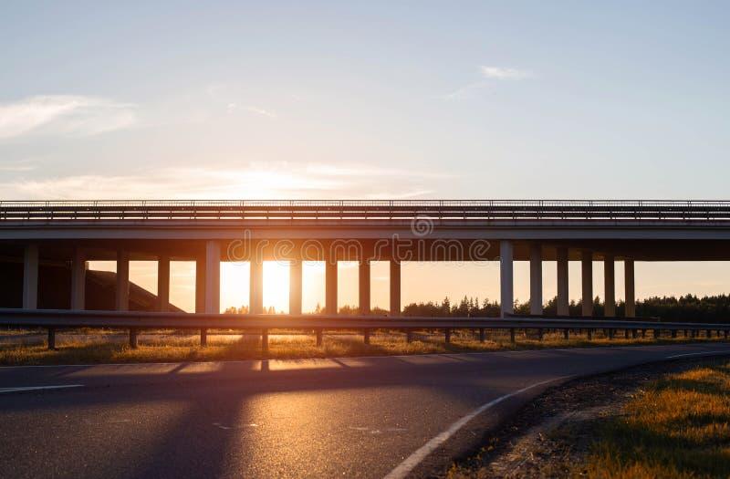 Γέφυρα μεταφορών σε μια οδική σύνδεση για την εκφόρτωση της κυκλοφορίας στο δρόμο, βράδυ, ηλιοβασίλεμα, διάστημα αντιγράφων στοκ φωτογραφίες