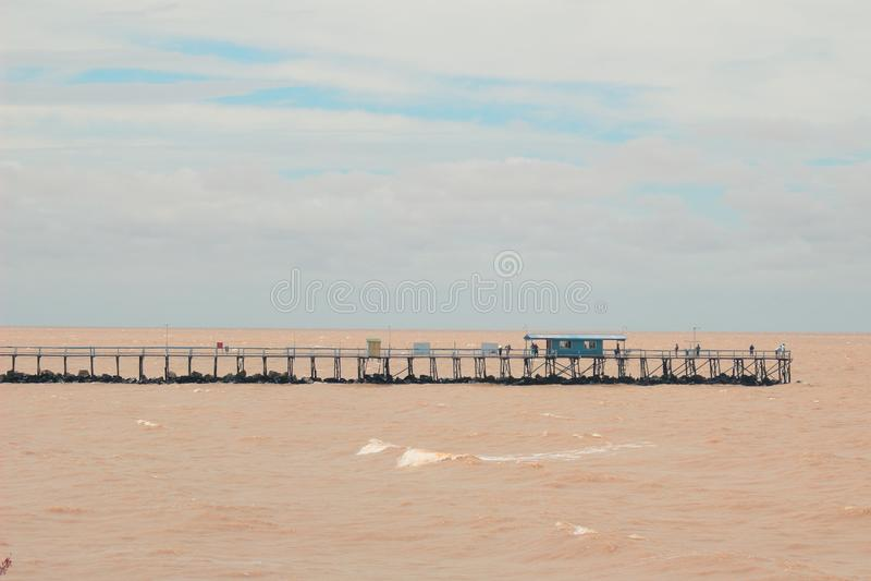 Γέφυρα πέρα από καφετί RÃo de Λα Plata στην Αργεντινή, Μπουένος Άιρες με ένα μικρούς μπλε σπίτι και έναν μπλε ουρανό στοκ εικόνες