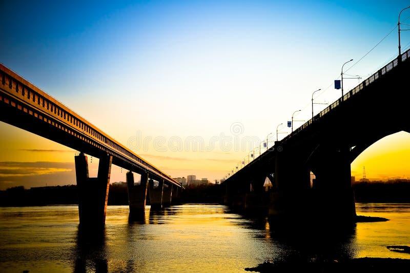 Γέφυρα πέρα από τον ποταμό στο ηλιοβασίλεμα στοκ εικόνα με δικαίωμα ελεύθερης χρήσης