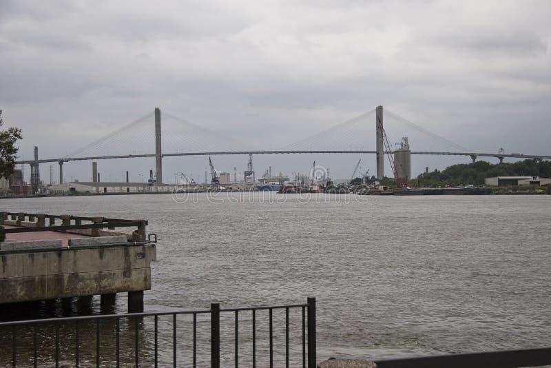 Γέφυρα που διασχίζει τον ποταμό σαβανών με τα βιομηχανικά κτήρια στο υπόβαθρο στοκ φωτογραφία με δικαίωμα ελεύθερης χρήσης