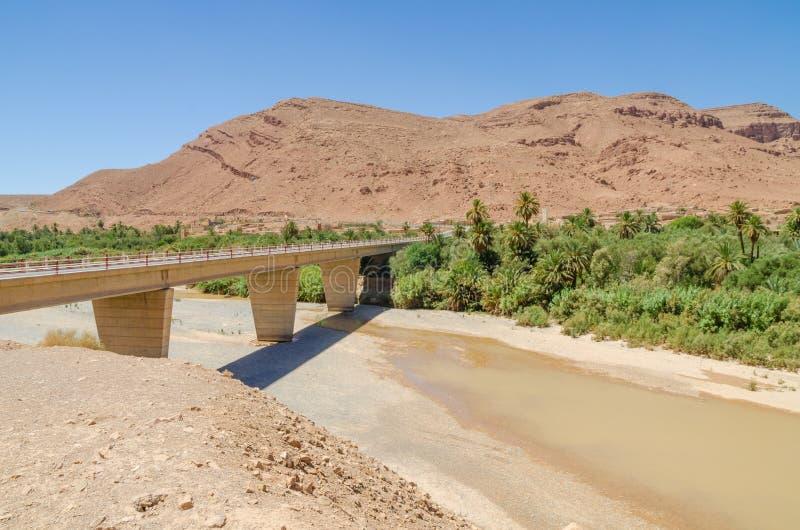 Γέφυρα που εκτείνεται πέρα από την ξηρά κοίτη του ποταμού με λίγο νερό, τα βουνά και τους φοίνικες στο Μαρόκο, Βόρεια Αφρική στοκ φωτογραφία με δικαίωμα ελεύθερης χρήσης
