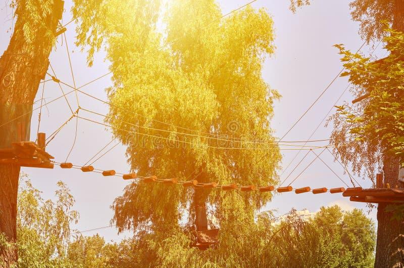 Γέφυρα σχοινιών με την ξύλινη σκάλα στο πάρκο περιπέτειας, επίδραση φωτός του ήλιου στοκ εικόνες