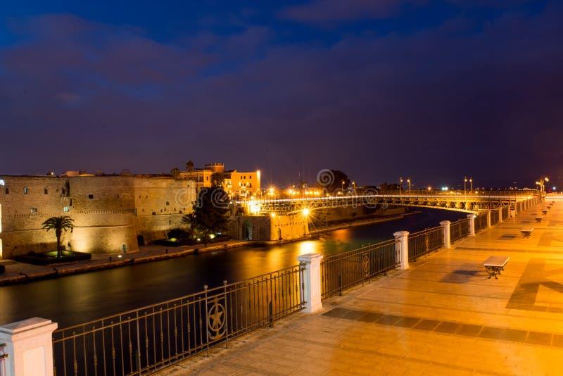 Γέφυρα ταλάντευσης του Taranto στη βάρκα καναλιών του Taranto τη νύχτα στοκ εικόνα