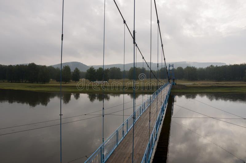 Γέφυρα του μπλε χρώματος πέρα από τον ποταμό και την αντανάκλασή του Γκρίζος ουρανός και γκρίζο νερό Πράσινο δάσος και montains μ στοκ φωτογραφία με δικαίωμα ελεύθερης χρήσης