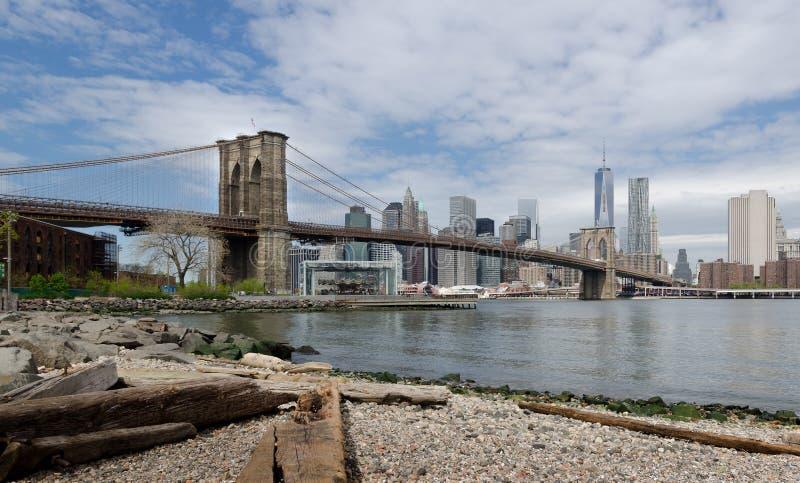 Γέφυρα του Μπρούκλιν και Λόουερ Μανχάταν από την παραλία Dumbo στοκ εικόνες